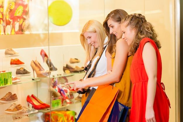 Acquisto della scarpa degli amici in un centro commerciale
