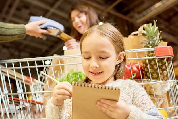 Acquisto di drogheria della bambina nel supermercato