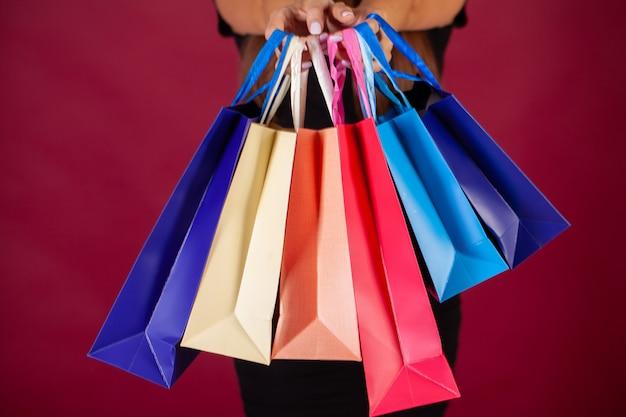 Acquisto, donna che tiene le borse colorate su rosso nella festa nera di venerdì