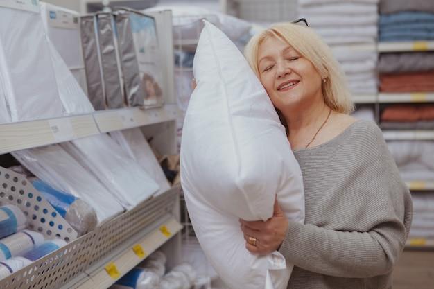 Acquisto maturo della donna al negozio di mobili