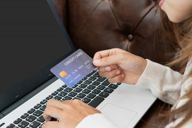 Acquisto online della donna asiatica con la carta di credito e la compressa che si siedono sul sofà a casa, stile di vita digitale con tecnologia, concetto di commercio elettronico