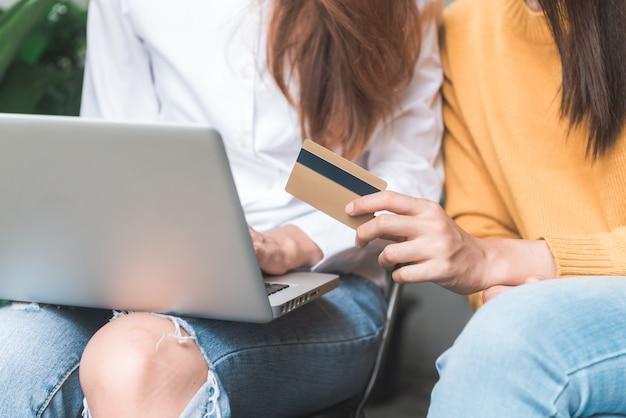 Acquisto online della donna asiatica facendo uso della carta di credito con il computer della compressa al ristorante del caffè