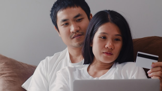 Acquisto online delle giovani coppie incinte asiatiche a casa. mamma e papà sentirsi felici utilizzando la tecnologia del computer portatile e il prodotto d'acquisto del bambino della carta di credito mentre si trovano sul sofà in salone a casa.