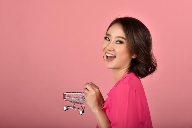 Acquisto online, donna asiatica felice che tiene carrello divertente del carrello, servizio di distribuzione e promozione di vendita con lo spazio della copia per annunciare.