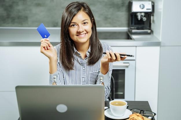 Acquisto online sorridente della donna facendo uso di un computer portatile dello smartphone e di una carta di credito a casa.