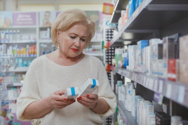 Acquisto senior adorabile della donna alla farmacia
