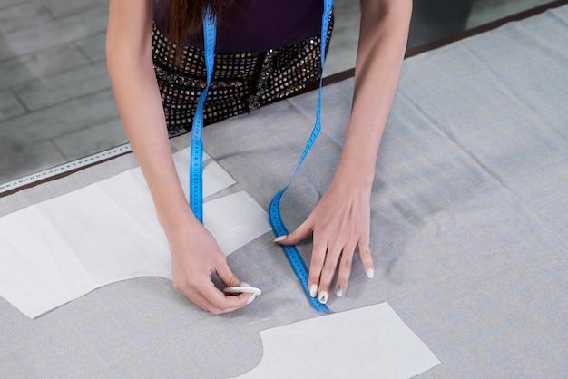 Adatta la linea di disegno sul tessuto con il gesso nello studio dell'atelier