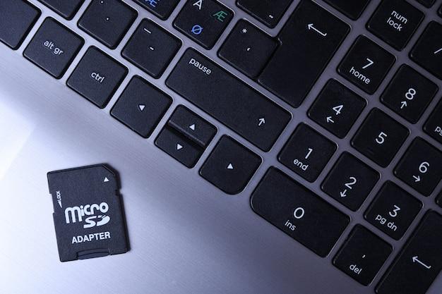 Adattatore per scheda di memoria micro sd sulla tastiera grigia del computer portatile sul tavolo di legno. avvicinamento