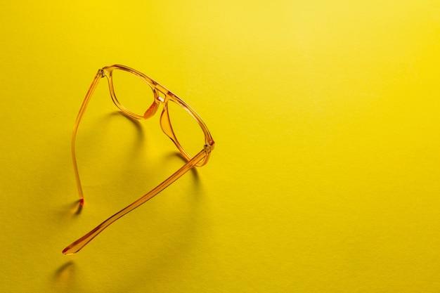 Adatti gli occhiali da sole femminili su fondo giallo astratto con lo spazio della copia