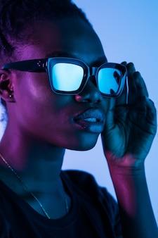 Adatti i giovani vetri africani di usura della donna della ragazza che esaminano la macchina fotografica isolata sullo spazio al neon
