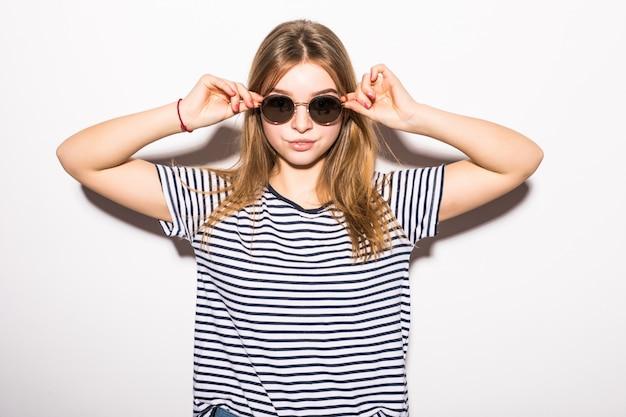 Adatti i pantaloni a vita bassa della giovane donna in occhiali da sole isolati sulla parete bianca