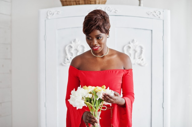 Adatti il modello afroamericano in vestito rosso da bellezza, donna sexy che posa i fiori della tenuta dell'abito da sera nella stanza d'annata bianca.