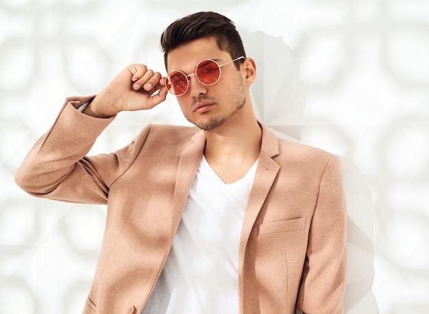 Adatti il modello alla moda vestito in vestito rosa-chiaro elegante che posa vicino alla parete bianca. metrosexual