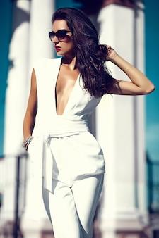 Adatti il modello sexy sexy della ragazza della donna di affari in vestito bianco in occhiali da sole nella via