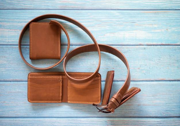 Adatti il portafoglio e la cinghia marroni su fondo di legno blu
