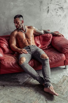 Adatti il ritratto del modello maschio nudo sexy con il tatuaggio e una barba nera che si siede nella posa calda sul sofà di cuoio rosso. interno camera soppalco con muro di cemento grigio.