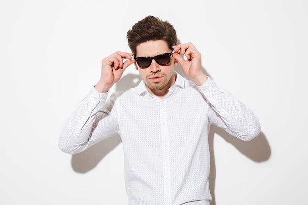 Adatti il ritratto del modello operato dell'uomo vestito in camicia che tocca gli occhiali da sole e che guarda la macchina fotografica con lo sguardo serio, sopra spazio bianco con ombra