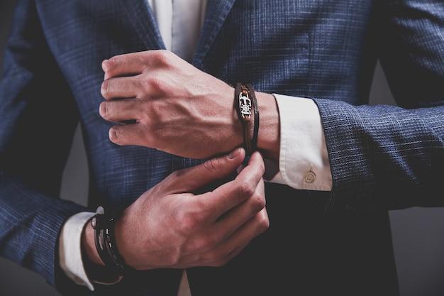 Adatti il ritratto dell'uomo di modello bello del giovane uomo d'affari vestito in vestito blu elegante su gray.