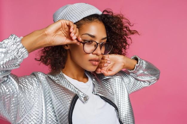 Adatti il ritratto della donna della corsa della miscela con pelle marrone e l'acconciatura africana riccia su fondo rosa vivo. indossa giacca invernale argento e cappello grigio.