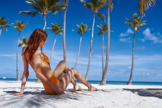 Adatti il ritratto della donna in costume da bagno giallo alla spiaggia