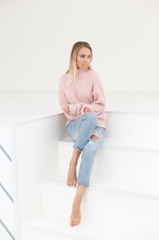 Adatti il ritratto della donna in maglione rosa e jeans strappati