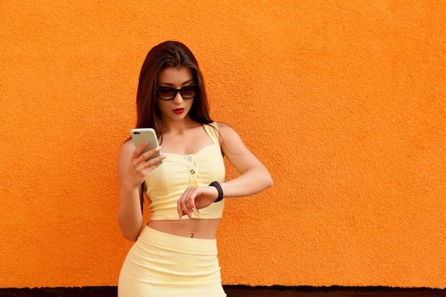 Adatti il ritratto della donna sorridente graziosa in occhiali da sole che stanno con lo smartphone