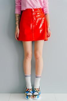 Adatti il ritratto della ragazza alla moda in scarpe alla moda e gonna rossa