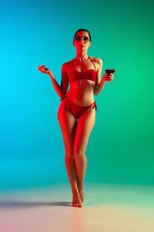 Adatti il ritratto della ragazza seducente in costumi da bagno alla moda che posano su una parete gialla luminosa. estate, stagione balneare