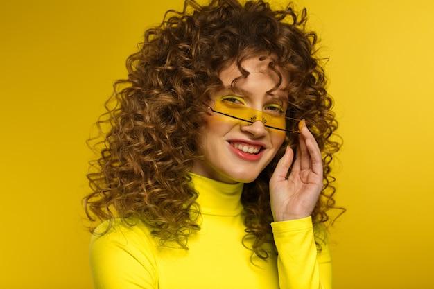 Adatti il ritratto dello studio di giovani belle donne con capelli ricci
