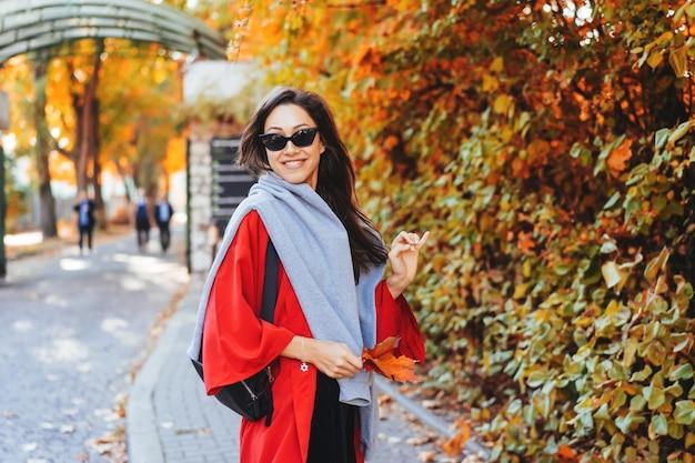 Adatti il ritratto di bella donna nel parco di autunno