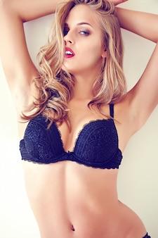 Adatti il ritratto di bello giovane modello biondo sexy della donna adulta che porta la biancheria erotica nera che posa nell'interno leggero di mattina