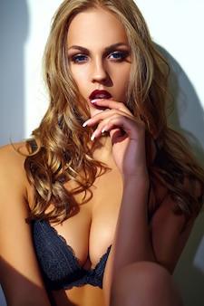 Adatti il ritratto di bello giovane modello biondo sexy della donna adulta che porta la biancheria erotica nera che posa vicino alla parete grigia