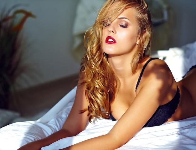 Adatti il ritratto di bello giovane modello biondo sexy della donna adulta che porta la biancheria erotica nera che si trova sul letto al tramonto