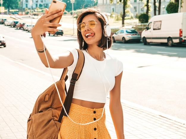 Adatti il ritratto di giovane donna alla moda dei pantaloni a vita bassa che cammina nella via ragazza che fa selfie il modello sorridente gode dei suoi fine settimana con lo zaino. donna che ascolta la musica tramite le cuffie
