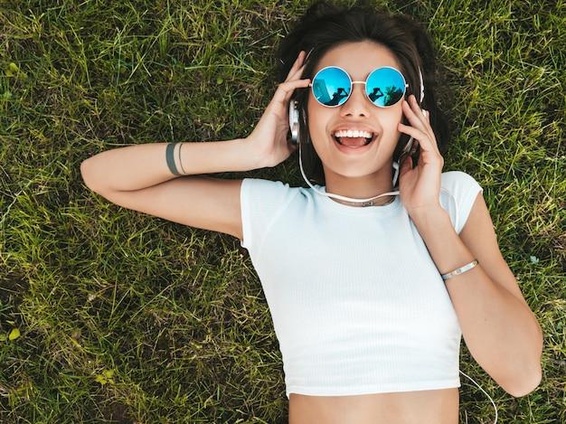 Adatti il ritratto di giovane donna alla moda dei pantaloni a vita bassa che si trova sull'erba nel parco la ragazza indossa l'attrezzatura d'avanguardia il modello sorridente gode dei suoi fine settimana. donna che ascolta la musica tramite le cuffie. vista dall'alto