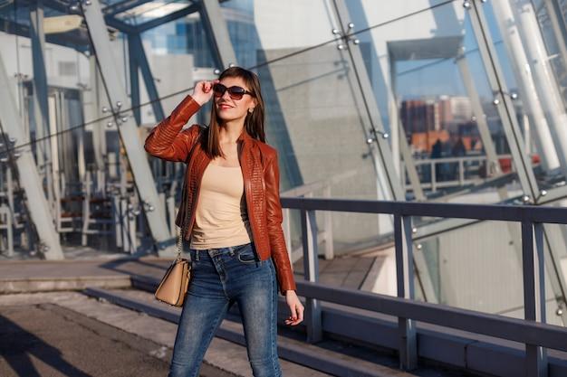 Adatti il ritratto di giovane donna di modello in bomber marrone, jeans e occhiali da sole su fondo urbano.
