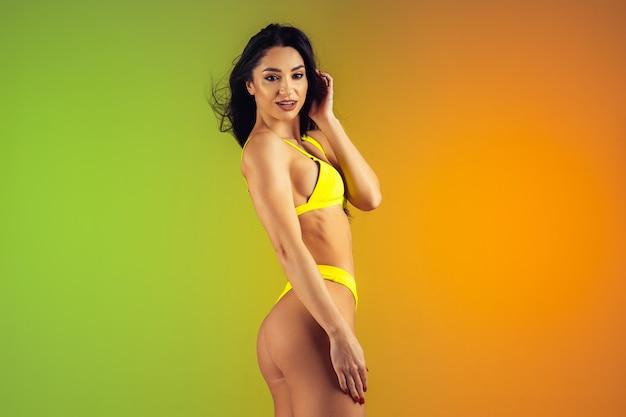 Adatti il ritratto di giovane misura e la donna allegra in costumi da bagno di lusso gialli alla moda sul fondo di pendenza. corpo perfetto pronto per l'estate.