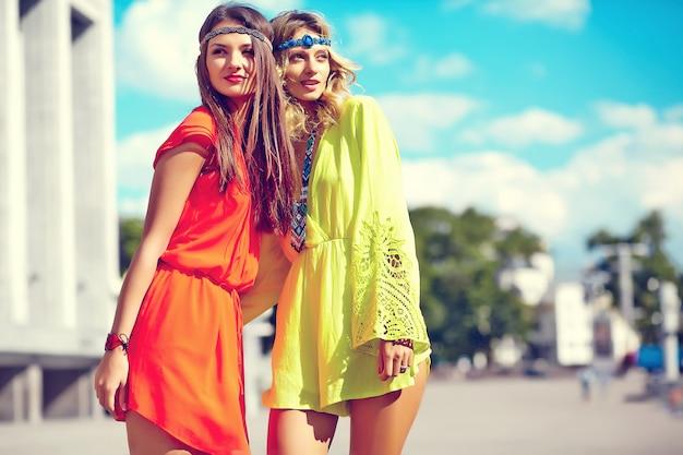 Adatti il ritratto di giovani modelli delle donne del hippie nel giorno soleggiato dell'estate in vestiti variopinti luminosi dei pantaloni a vita bassa