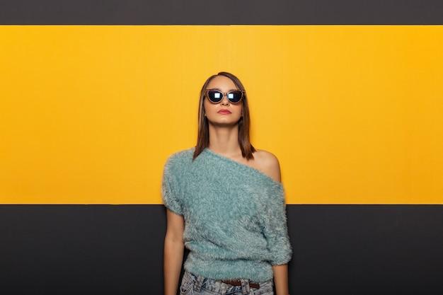 Adatti il ritratto di una donna attraente e alla moda con gli occhiali da sole
