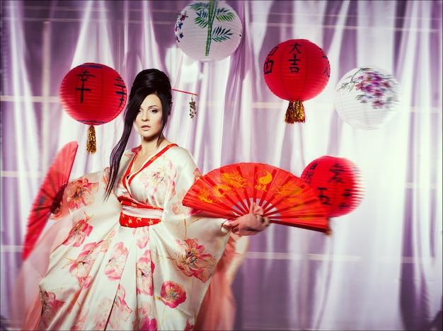 Adatti il ritratto di una giovane bella bruna nello stile giapponese come una geisha
