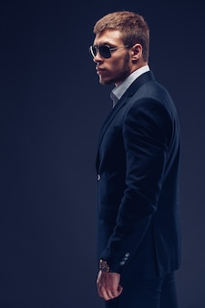 Adatti il vestito nero del giovane uomo d'affari su fondo scuro