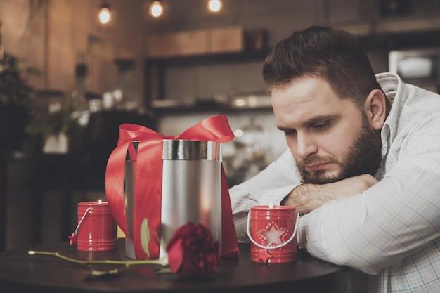Adatti l'uomo barbuto che aspetta una ragazza in un caffè