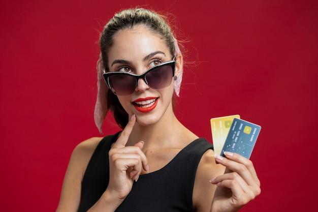 Adatti la donna che mostra il suo primo piano delle carte di credito