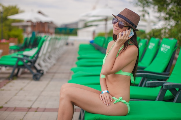 Adatti la donna che parla sul telefono mentre si siedono al lettino della piscina