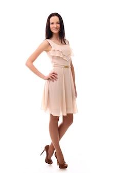 Adatti la donna che posa con il vestito nel colore di rosa pastello, isolato