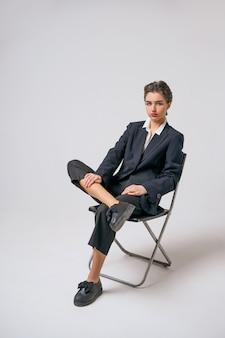 Adatti la donna che si siede in un vestito su una sedia su una priorità bassa bianca, su un trucco luminoso e sui capelli corti
