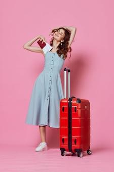 Adatti la donna di viaggio con la valigia rossa in vestito blu