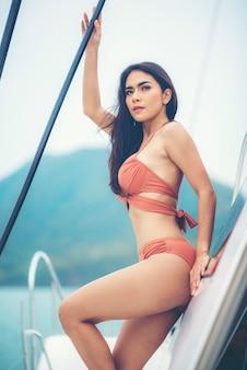 Adatti la foto all'aperto dell'estate della ragazza sexy con capelli scuri in bikini lussuoso che si rilassa sull'yacht nel mare
