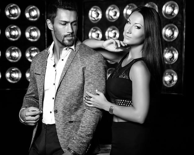 Adatti la foto dell'uomo elegante bello in vestito con la bella donna sexy che posa sul fondo nero delle luci dello studio