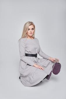 Adatti la foto di bella giovane donna bionda elegante in una borsa della tenuta del vestito grigio che posa sopra la parete grigia. foto di moda primavera estate